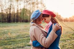 Senior mother and her adult daughter hugging in spring forest. Mother`s day concept. Family values stock photo