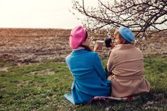 Senior mother and her adult daughter sitting and drinking coffee by river. Mother`s day concept. Family values stock photography