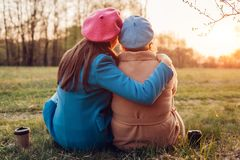 Senior mother and her adult daughter sitting and hugging in spring forest. Mother`s day concept. Family values stock image