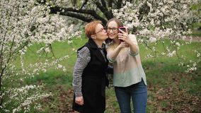 Senior mother and her adult daughter taking selfie in blooming garden. Senior mother and her adult daughter hugging and taking selfie in blooming garden. Mother stock video