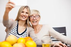 Senior mother and her daughter smiling and taking a selfie while sitting by dinner table in bright room royalty free stock photography