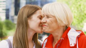 Senior mother and her young daughter standing on street. Happy family enjoying time together stock footage