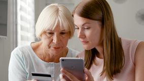 Senior mother and her young daughter using smartphone at home. Shopping with credit card on cellphone. Teen granddaughter teaching grandmother how to use stock video footage