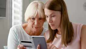 Senior mother and her young daughter using smartphone at home. Shopping with credit card on cellphone stock footage