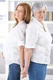 Senior mother and pregnant daughter smiling stock images