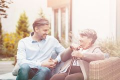 Senior mother and son talking while sitting on a wicker sofa outdoor stock photo