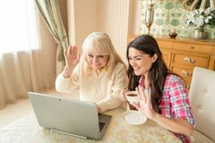 Senior mother together with her daughter waving at laptop camera. Two Lovely Women Wave To The Laptop Camera, Greeting A Friend. Smiling Daughter With A Cup Of stock photography