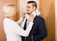 Senior mother tying a scarf to son Stock Photography