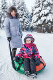 Senior mother and young child portrait with snow tubing Royalty Free Stock Photography