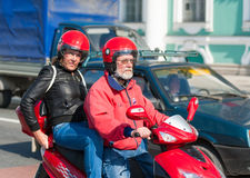 Senior motorcyclists. ST PETERSBURG - JUNE 29, 2011: Unidentified man and woman (in their 50s presumably) go by motorcycle in the downtown. Due to climate stock photography