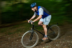 Senior on a mountainbike. Senior cycling on a mountain bike through the forest Stock Images
