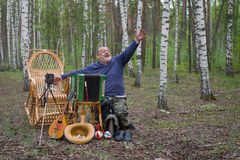 Senior musician invites people in park Royalty Free Stock Images