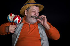 Senior musician with mouth-organ and maraca Royalty Free Stock Photography