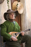 Senior musician playing mandolin. Taggia, Italy - March 1, 2015: Participant of medieval costume party. For over 30 years, in the historic city of Taggia Royalty Free Stock Photos