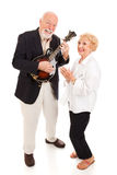 Senior Musicians. Senior man plays mandolin while his wife sings along.  Full body isolated Stock Photography