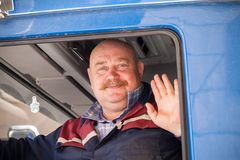 Senior mustached truck driver smiles. Saint-Petersburg, Russia - May 30, 2015: Senior mustached truck driver smiles and says hello from his blue lorry cabin Stock Photography