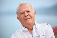 Senior near seacoast, inclined head aside Stock Photos