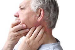 Senior with neck and jaw stiffness. Older man has difficulty moving his neck or jaw Royalty Free Stock Image