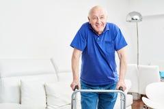 Senior nella riabilitazione impara la camminata con il camminatore fotografia stock libera da diritti