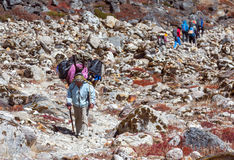Senior Nepalese Porter carrying Luggage and group of Tourists Stock Image
