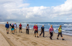 Senior nordic walkers on the beach. Kijkduin beach, the Netherlands - September 03, 2016: senior nordic walkers on the beach Royalty Free Stock Photo