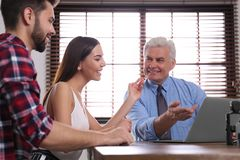 Senior notary working with young couple