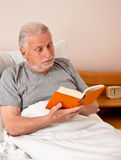 Senior in the nursing home to read the book in bed Stock Photos