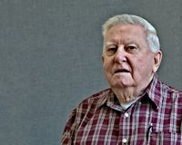 Senior octogenarian old man in plaid with gray background. royalty free stock photography
