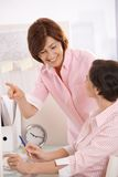 Senior office worker teaching coworker in office. Smiling, pointing Royalty Free Stock Photo