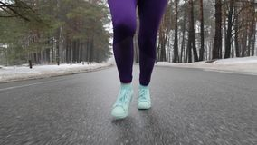 Senior old Caucasian girl running in the snowy park in winter with headphones. Legs Close up front follow shot. Senior old Caucasian girl running in the snowy stock video footage