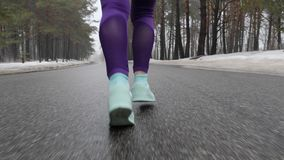 Senior old Caucasian girl running in the snowy park in winter. Legs Close up Back follow shot.  stock footage