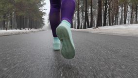 Senior old Caucasian girl running in the snowy park in winter. Legs Close up Back follow shot. Slow Motion.  stock video