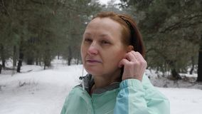 Senior old Caucasian woman puts in earphones before running in the snowy winter park. Close up Front shot.  stock footage