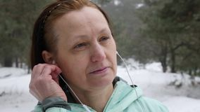 Senior old Caucasian woman puts in earphones before running in the snowy winter park. Close up Front shot.  stock video footage