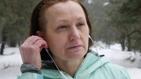 Senior old Caucasian woman puts in earphones before running in the snowy winter park. Close up Front shot.  stock video