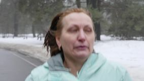 Senior old Caucasian woman running in the snowy park in winter. Close up front follow shot.  stock video