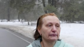 Senior old Caucasian woman running in the snowy park in winter. Close up front follow shot. Slow Motion.  stock video