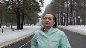 Senior old Caucasian woman running in the snowy park in winter with headphones. Close up front follow shot.  stock footage