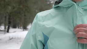 Senior old Caucasian woman  zips her jacket before running in the snowy winter park. Close up Front shot.  stock footage