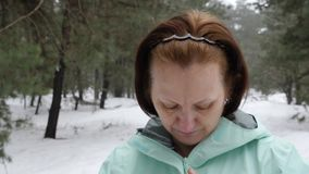 Senior old Caucasian woman  zips her jacket before running in the snowy winter park. Close up front shot.  stock video footage