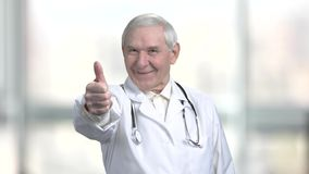 Senior old doctor in white coat and stethoscope shows thumb up. Fist with thumb up turning rotation, blurred windows background