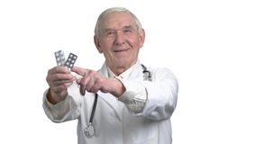 Senior old grey hair doctor in uniform pointing a medicine in strip. Portrait of elder man with white coat and stethoscope in white isolated background stock footage