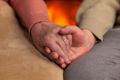 Senior old hands holding in front of fireplace Royalty Free Stock Photo
