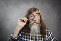 Senior old man looking through zoom magnifying gla. Ss. Funny elder amazement investigation or test vision loss Royalty Free Stock Photos
