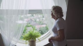 Senior woman sadly looking through window.
