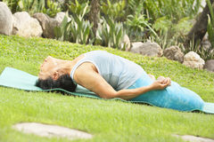 Senior old woman doing yoga in park Stock Image