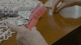 Senior old woman hands putting pills in an organizer box by the days of the week at home -. Senior old woman hands putting pills in an organizer box by the days stock footage