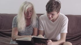 Senior old woman sitting with grandson at sofa at home and looking through family photo album for good memories. Indoor. Shooting of retired aged woman. Social stock video footage