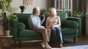 Senior older family couple having trust conversation sitting on sofa