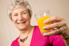Senior older lady with glass of orange juice Stock Photography